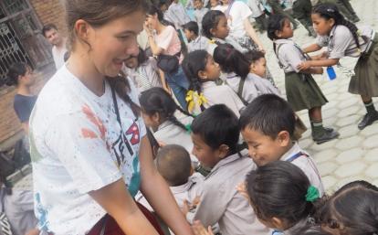 ネパールの子供たちとハイタッチをする高校生ボランティア